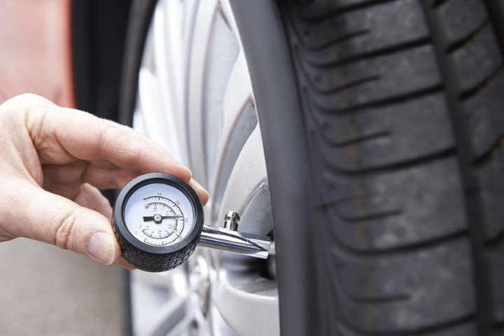 Checking tire pressure. Tires are also sold on BE FORWARD Auto Parts.