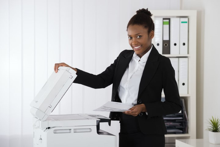 Young Businesswomen Using a Copier - BE FORWARD